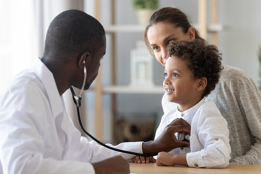 Employee Benefits - Pediatrician Listening to a Young Happy Child with Stethoscope While Child is Being Held by Mother